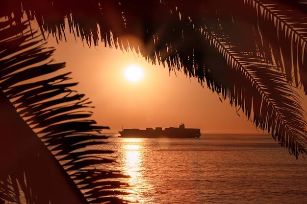 Ein großes schiff am horizont im atlantik unter der hellen sonne und dem roten sonnenuntergang. sonnenlichtreflexion vom wasser