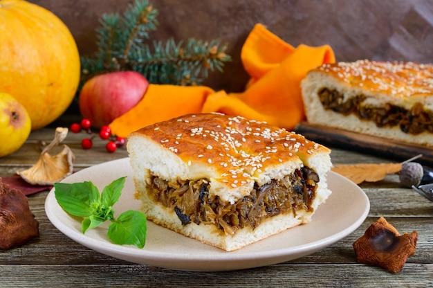 Ein großes stück leckerer kuchen mit kohl und waldpilzen auf einer teller-nahaufnahme. herbstthema.