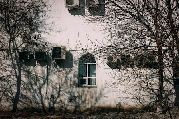 Ein großes wohnhaus mit anzeichen von wetter mit klimaanlagen von außen hängen.