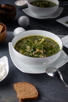 Ein grüner borschtsch der vorderansicht, gesalzen mit gemüse und brotlaib innerhalb der flüssigen mahlzeit der weißen plattensuppe