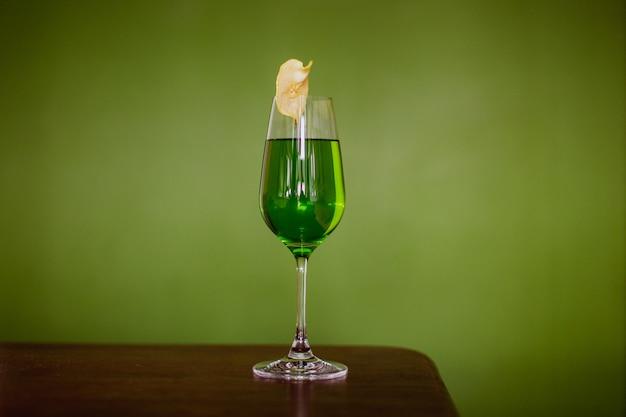 Ein grüner cocktail in einem flötenglas, garniert mit einer dehydrierten apfelscheibe