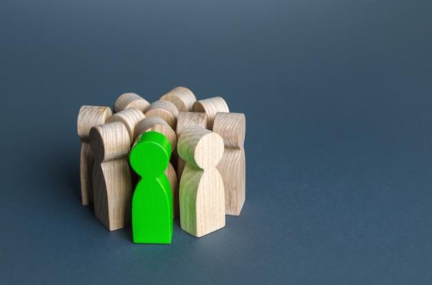Ein grüner mann steht in einer menschenmenge, die einen talentierten kandidaten rekrutiert, der nach einer person sucht
