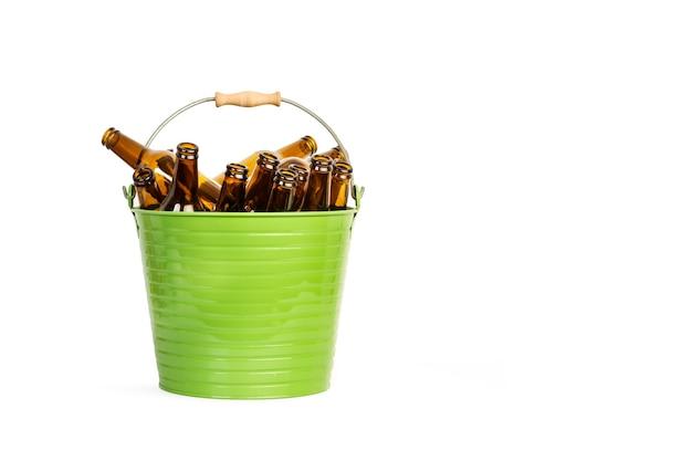 Ein grüner metalleimer mit vielen leeren bierflaschen auf einem weißen