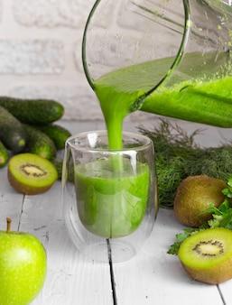 Ein grüner smoothie wird auf hellem hintergrund aus einem mixer in ein glasglas gegossen. gesundes essen kochen. kiwi, äpfel, gurken und grüns.