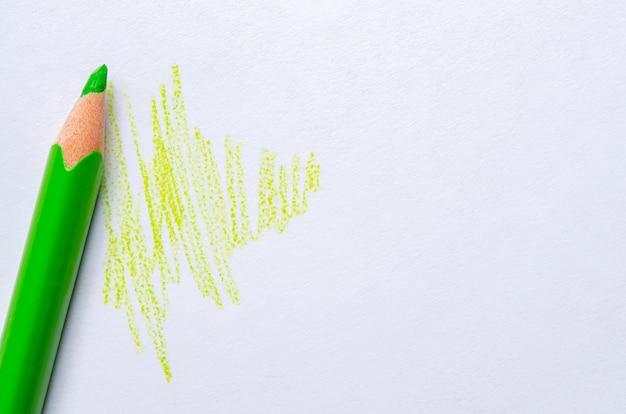 Ein grüner stift zeichnet striche auf weißem papier. speicherplatz kopieren.