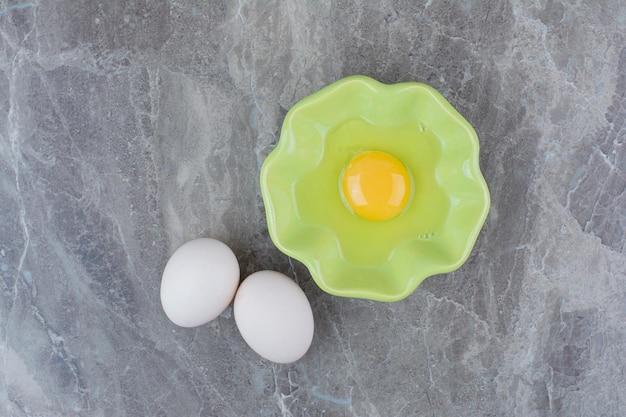 Ein grüner teller mit rohem ei und hühnereiern. foto in hoher qualität