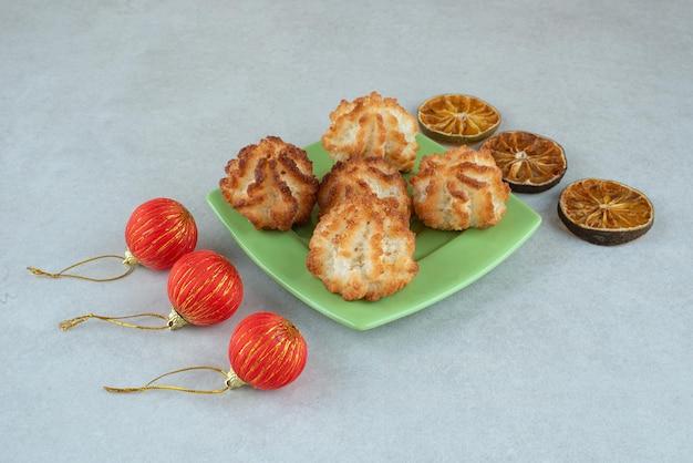 Ein grüner teller mit runden süßen keksen mit getrockneten orangen und weihnachtskugeln.
