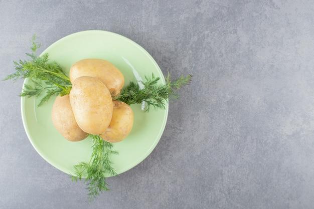 Ein grüner teller mit ungekochten kartoffeln mit frischem dill.