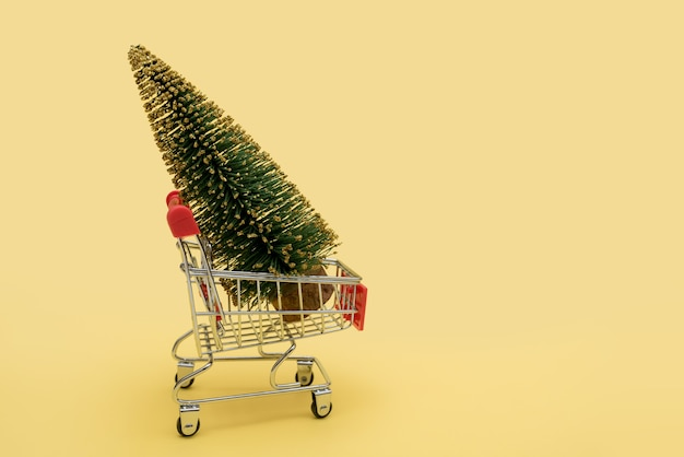 Ein grüner weihnachtsbaum in einem supermarktwagen.