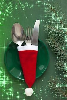 Ein grüner weihnachtsteller und besteck sind mit einem roten schal auf grünem grund mit einem fichtenzweig als menügestaltungselement gebunden