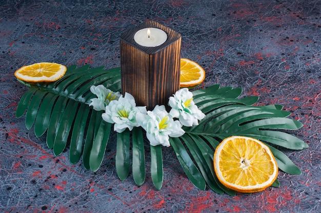 Ein grünes blatt mit kerze und geschnittenen getrockneten orangenfrüchten auf grau