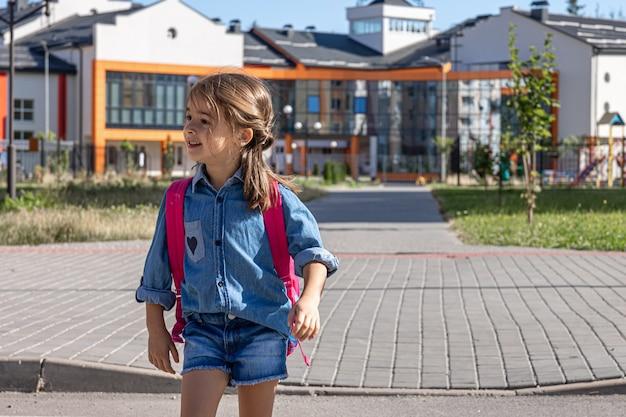 Ein grundschüler geht nach der schule, dem ersten schultag, nach hause, zurück in die schule.