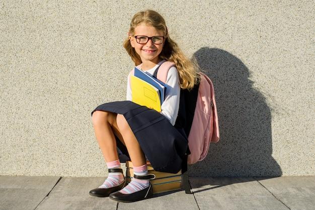 Ein grundschüler mit notizbüchern in der hand