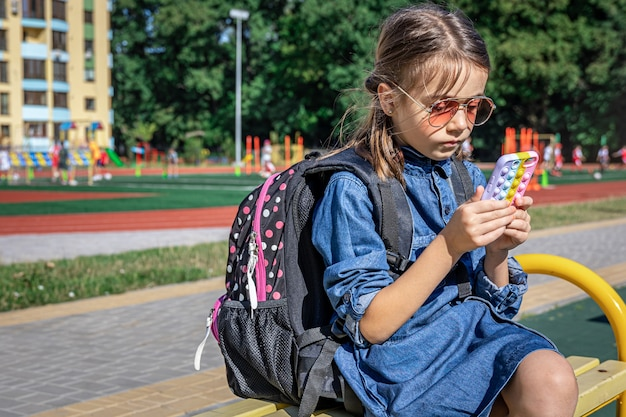 Ein grundschüler mit rucksack benutzt ein smartphone und sitzt in der nähe der schule.