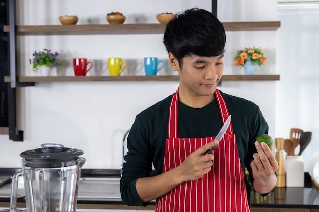 Ein gutaussehender asiatischer mann betrachtet lemmonfrucht in seiner hand und die andere hand hält ein messer in der modernen küche.