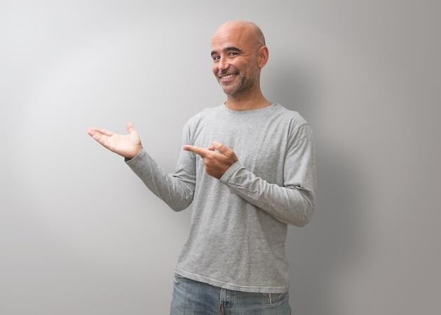 Ein gutaussehender glatzköpfiger mann, der gesten des erfolgs macht