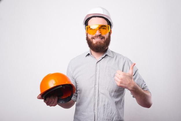 Ein gutaussehender ingenieur trägt einen helm und eine schutzbrille. wenn er einen anderen helm hält, zeigt er einen daumen nach oben und lächelt in die kamera