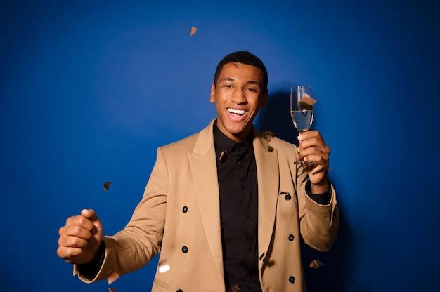 Ein gutaussehender junger mann mit einem glas champagner