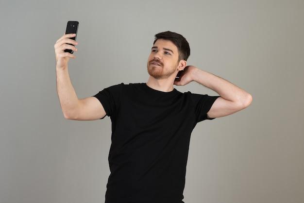 Ein gutaussehender kerl, der selfie auf einem grau macht.