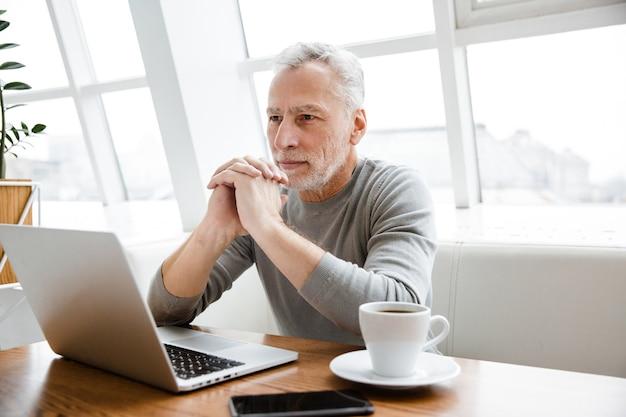 Ein gutaussehender konzentrierter reifer senior geschäftsmann sitzt im café mit laptop-computer.