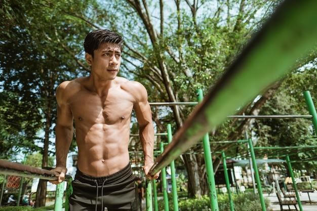 Ein gutaussehender mann, der klimmzüge macht, um ausdauer und rückenmuskulatur zu trainieren, während er draußen im park mit exemplar trainiert