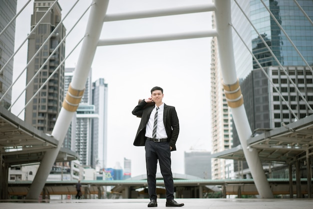 Ein gutaussehender mann, der schwarzen anzug und weißes hemd trägt, hält eine handtasche und steht in der stadt.