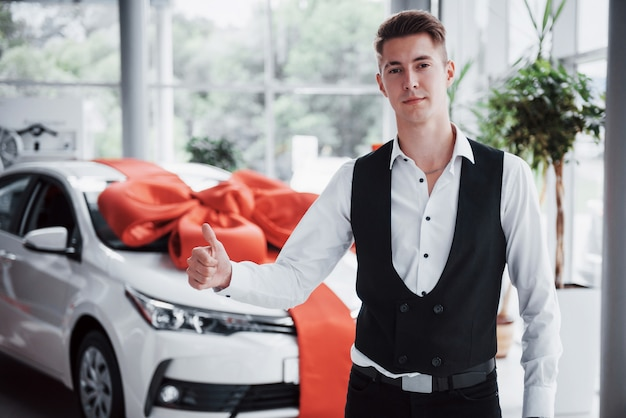 Ein gutaussehender mann ist ein käufer, der neben einem neuen auto im händlerzentrum steht und in die kamera schaut.