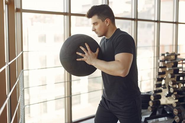 Ein gutaussehender mann ist in einem fitnessstudio beschäftigt