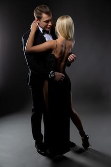 Ein gutaussehender mann knöpft das kleid seiner sexy blonden lieblingsfrau während einer zärtlichen umarmung auf. foto auf dunkler oberfläche