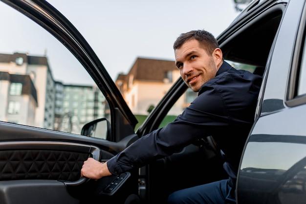 Ein gutaussehender mann schaut aus seinem auto und schaut zurück. der fahrer befindet sich in einem wohngebiet der stadt