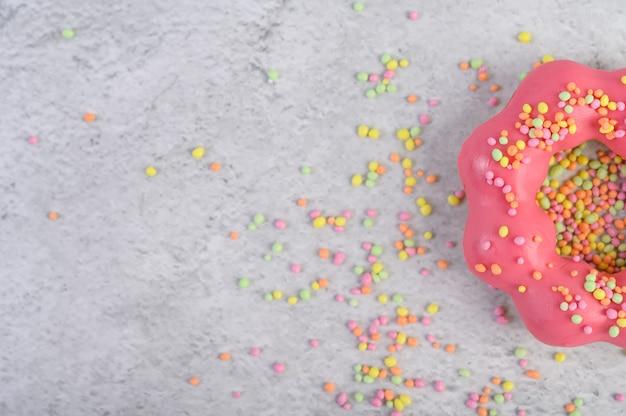 Ein halber erdbeerdonut, mit zuckerguss dekoriert und auf den boden gestreut