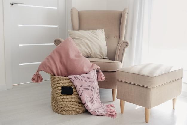 Ein handgefertigter jutekorb mit einer kleinen schwarzen tafel und kissen und einer rosa decke auf dem boden neben einem beigen sessel mit einem hocker auf einer weißen tapetenoberfläche. gemütliches wohnkonzept
