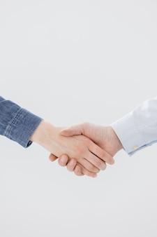 Ein handschlag von zwei personen, einem mann und einer frau geschäftspartner grüßen