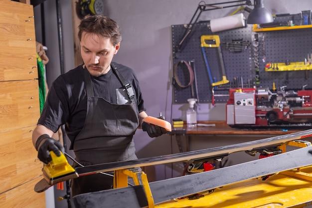 Ein handwerker in der werkstatt, der ski repariert