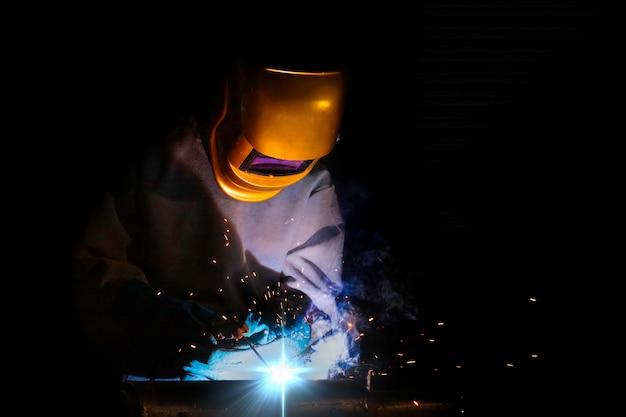 Ein handwerker schweißt mit werkstückstahl.arbeiter über schweißerstahl elektroschweißgerät verwenden in der fabrikindustrie treten lichtlinien und sicherheitsausrüstung aus.