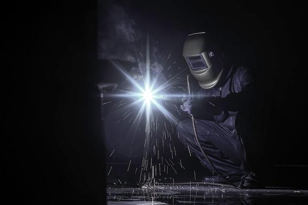 Ein handwerker schweißt mit werkstückstahl. arbeiter über schweißerstahl unter verwendung des elektrischen schweißgeräts und der sicherheitsausrüstung in der fabrikindustrie. tonfarbe grau.