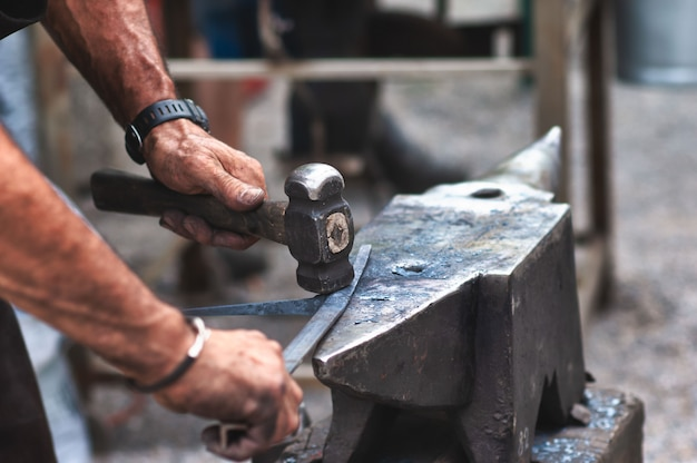 Ein handwerklicher schmied klopft mit einem hammer auf eisen, um ihn zu formen