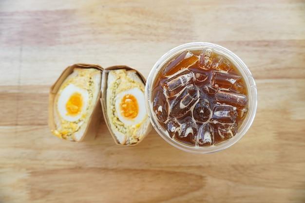Ein hartgekochter eierkohl mit ei-mayonnaise-sandwich nach koreanischer art mit einem eisgekühlten americano