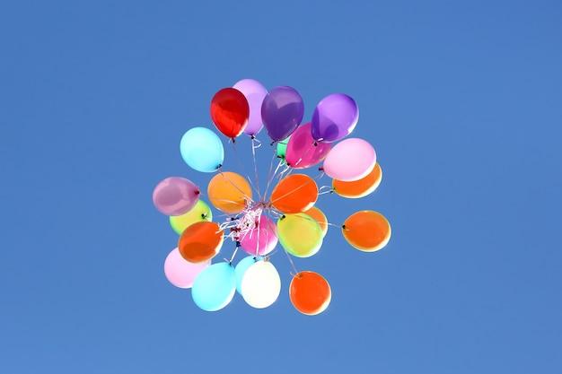 Ein haufen bunter luftballons gegen den blauen himmel. weihnachtsdekorationen