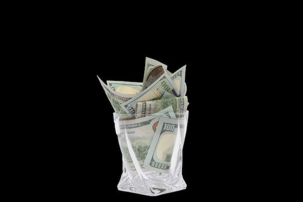 Ein haufen dollar, die in einem whiskyglas auf einem schwarzen, isolierten hintergrund gestapelt sind