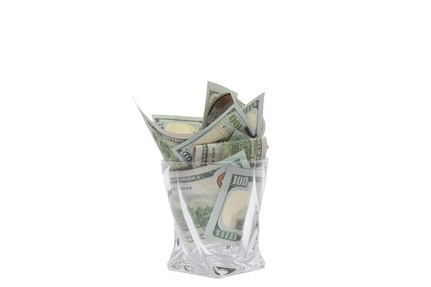 Ein haufen dollar, die in einem whiskyglas auf einem weißen, isolierten hintergrund gestapelt sind