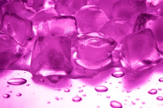 Ein haufen eiswürfel in lila auf einem reflektierenden tisch
