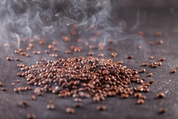 Ein haufen frisch gerösteter kaffeebohnen auf einem dunklen hintergrund