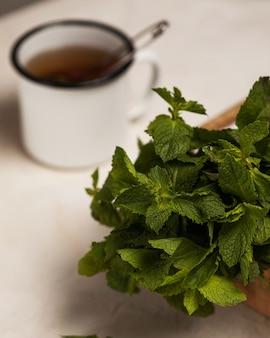 Ein haufen frischer grüner minze nahaufnahme hinter einer tasse mit schwarzem tee
