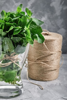 Ein haufen frischer minze in einer glasvase mit wasser, bio-produkten für den laden, öko-verpackungen, lebensmittellieferung.