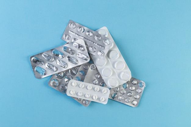 Ein haufen gebrauchte blisterpackungen mit pillen auf blauem hintergrund. medizinische blisterpackungen geöffnet und leer ohne pillen-draufsicht. medizin- und gesundheitskonzept.