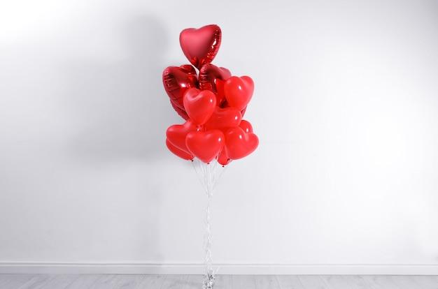 Ein haufen herzförmiger ballons in der nähe der weißen wand. valentinstag feier