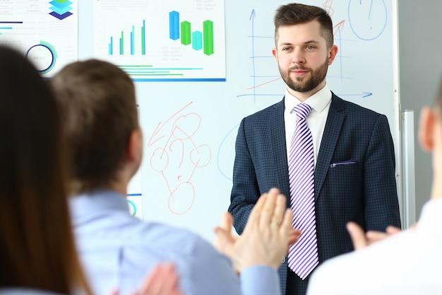 Ein haufen leute, die mann in anzug und krawatte zuhören und etwas erzählen