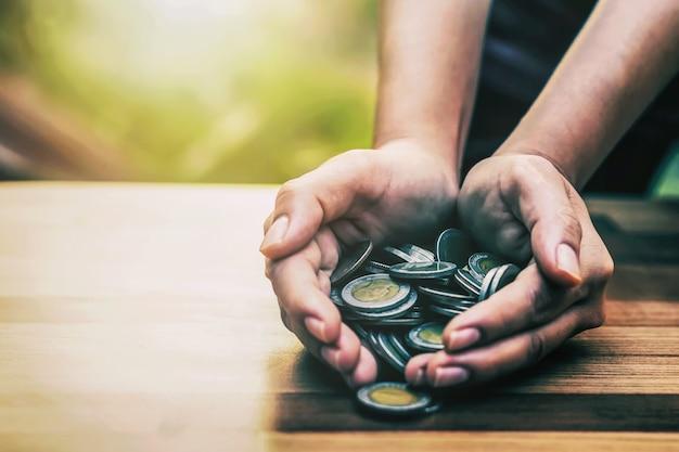 Ein haufen münzen in der hand geldsparkonzept