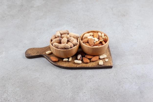 Ein haufen nüsse füllte sich und stapelte sich um mehrere schalen auf einem holzbrett auf marmorhintergrund. hochwertiges foto